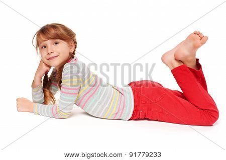 Side view of smiling child girl lying on stomach