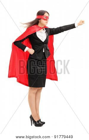 Full length profile shot of a serious female superhero holding her fist in the air isolated on white background