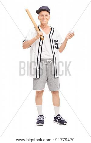 Full length portrait of an active senior in baseball jersey holding a baseball bat and a ball isolated on white background