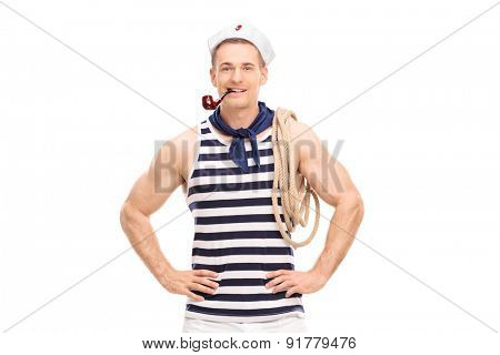 Handsome sailor with a rope around his shoulder smoking a pipe and looking at the camera isolated on white background