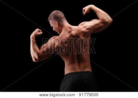 Rear view shot of a handsome bodybuilder flexing his shoulders and back muscles on black background