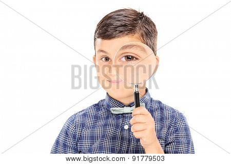 Cute little boy looking through a magnifying glass and smiling isolated on white background