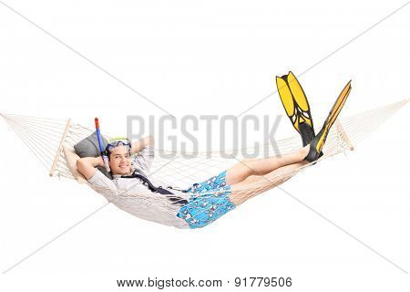 Joyful young man with diving equipment lying in a hammock and looking at the camera isolated on white background