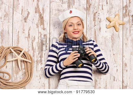Female sailor lying on a deck with binoculars in her hand and looking at the camera