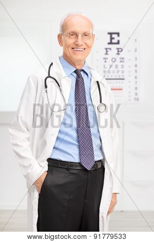 Vertical shot of a senior optician in a white coat posing in his office in front of an eyesight test and smiling