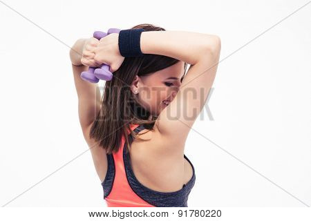 Back view portrait of a fitness woman working out with dumbbells isolated on a white background