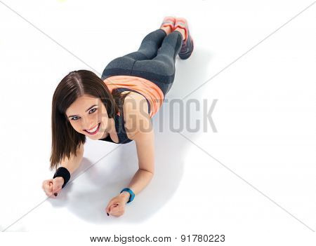 Happy sporty woman doing exercises on the floor isolated on a white background. Looking at camera