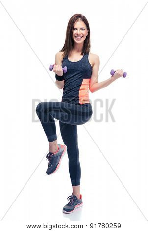 Full length portrait of a smiling woman working out with dumbbells isolated on a white background. Looking at camera