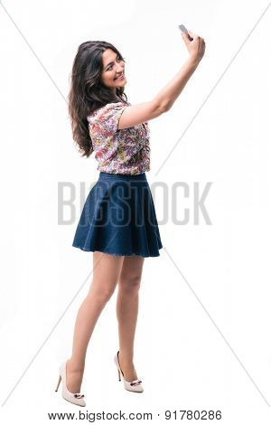 Full length portrait of elegant woman making selfie photo on smartphone isolated on a white background