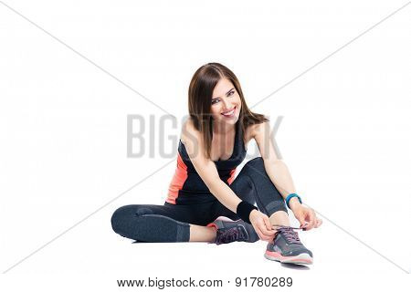 Happy sporty woman tying shoelaces isolated on a white background. Looking at camera