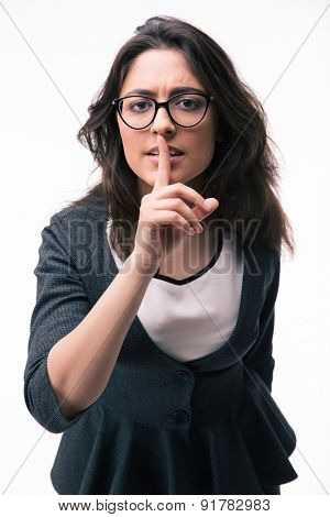 Businesswoman in glasses showing finger over lips isolated on a white background. Be quiet!!! Looking at camera