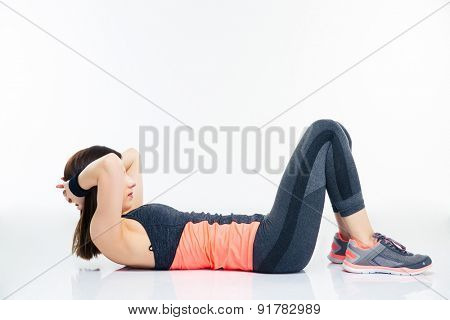 Fitness woman working out on the floor isolated on a white background
