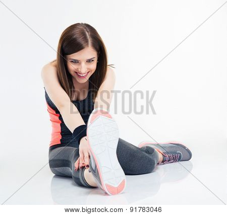 Smiling fitness woman doing stretching exercises isolated on a white background