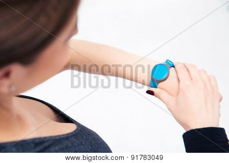 Sporty woman using activity tracker isolated on a white background