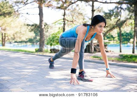 Fitness woman runner in start position outdoor