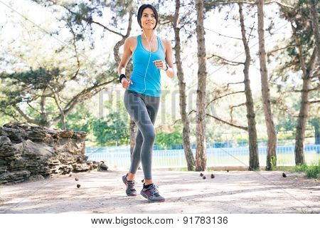 Full length portrait pf a happy fitness woman running outdoors in park