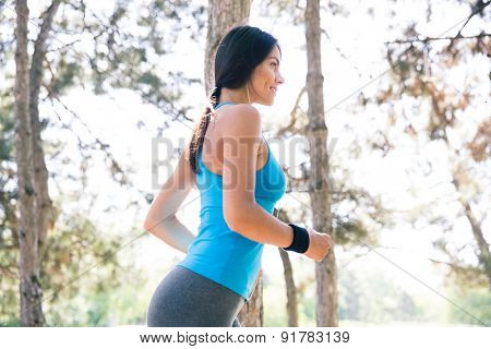 Happy young sports woman running outdoors in park