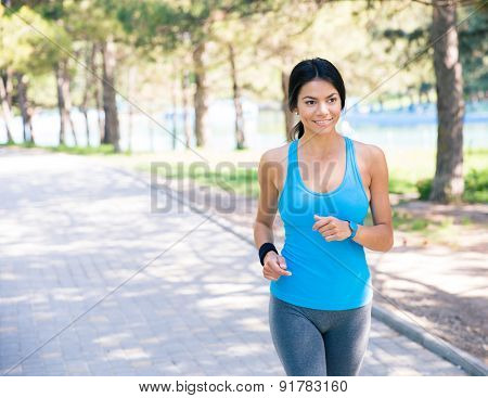 Smiling sporty woman running outdoors in park