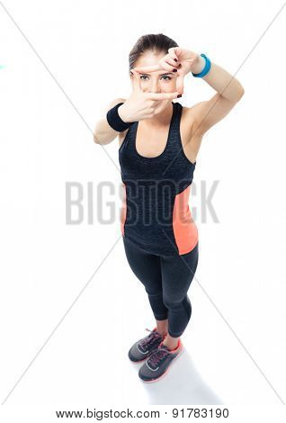 Full length portrait of a sporty young woman making frame with fingers and looking through frame at camera