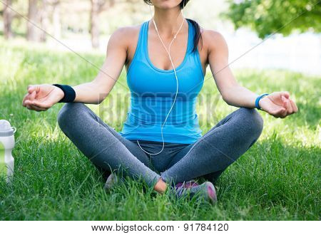 Crop image of a sporty woman meditating on the green grass in park