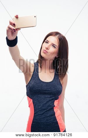 Beautiful fitness woman making selfie photo isolated on a white background