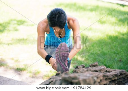 Sporty young woman stretching legs outdoors in park