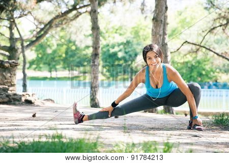 Fitness woman doing stretching exercise outdoors in park and looking at camera