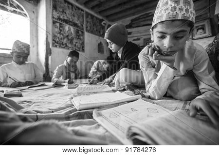 KATHMANDU, NEPAL - CIRCA DEC, 2013: Unknown children doing homework at Jagadguru School. School established at 2013, to let new generation learn Sanskrit and preserve Hindu culture.