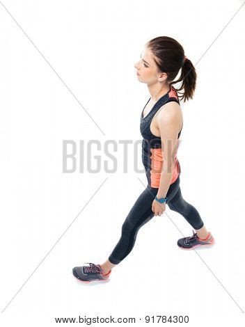 Full length portrait of a sporty woman walking isolated on a white background