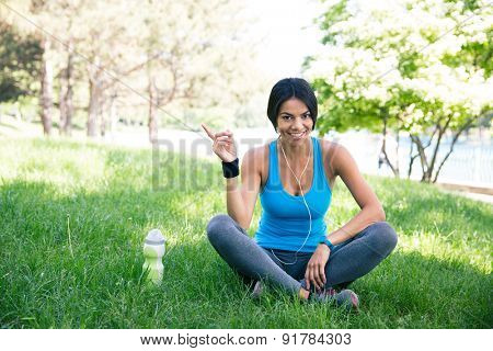 Happy fitness woman sitting on the green grass outdoors in park