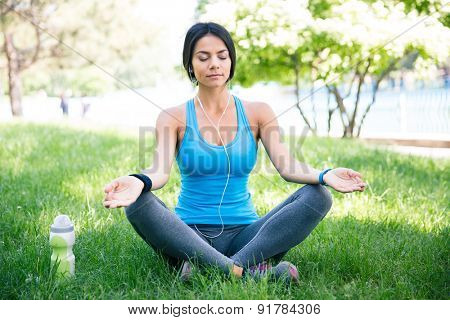 Fitness woman meditating on the green grass