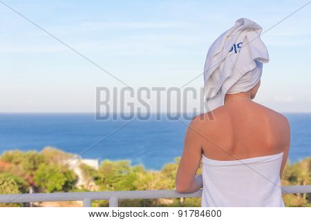 young woman looking at tropical sea view from a terrace in a resort