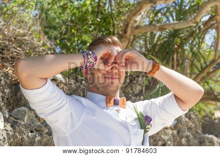 young happy groom looking for brie on natural background