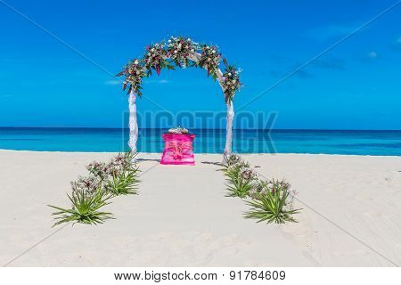 wedding arch and flower decoration, venue, setup on tropical beach, outdoor beach wedding