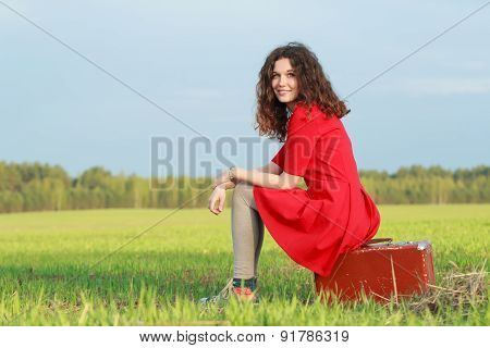 Smiling Brunette Girl Is Sitting On Old Leather Suitcase At The Edge Of Spring Farm Field