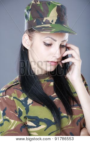 Image of attractive female soldier talking on cell phone against gray background
