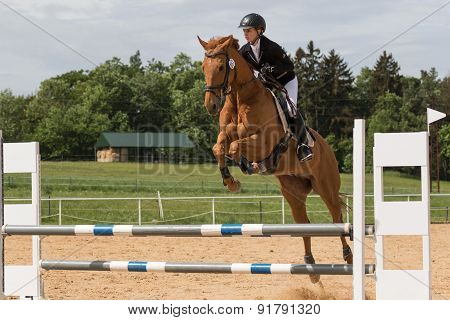 Young Horsewoman Is Jumping Over The Hurdle