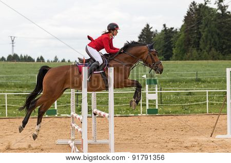 Horsewoman In Red Jacket Is Jumping Over A Hurdle