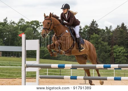 Closeup View Of Young Blonde Horsewoman Jumping