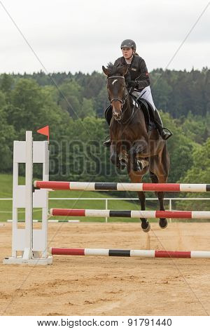 Front View Of Young  Horsewoman Jumping. Vertically.