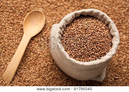 Buckwheat In Linen Sack With Wooden Spoon.