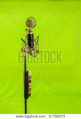 Vocal condenser microphone with wind screen isolated on green background