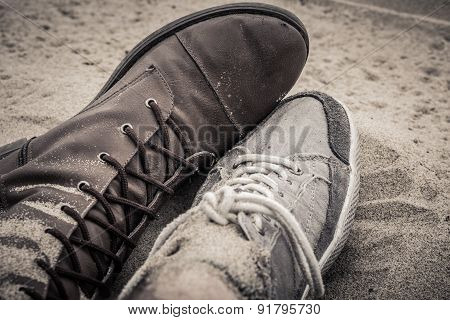 Shoes of man and woman lying next to each other on the sand