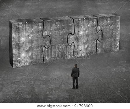 Man Facing Four Huge Concrete Puzzles Connected Together