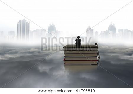 Pondering Man Sitting On Stack Of Books With Cityscape Cloudscape