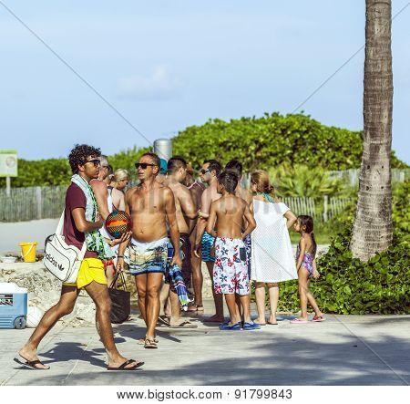 People Walk Along The Promenade At Ocean Drive In South Beach
