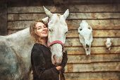 foto of horse face  - Young woman and her cremello horse on the background of horse and deer skulls
