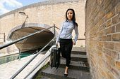 picture of carry-on luggage  - Full length portrait of young businesswoman with luggage walking down stairs - JPG