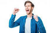 picture of excite  - Excited young man keeping arms raised and expressing positivity while standing against white background - JPG