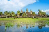 picture of raider  - Angkor Wat Temple and palm trees with front lake in sunny day  - JPG